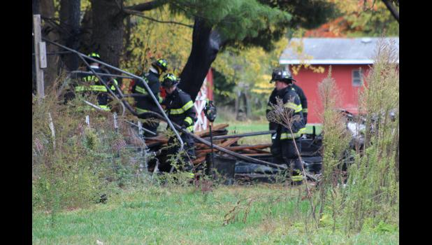 COMMERCIAL-NEWS   ROBERT TOMLINSON - Three Rivers Fire Department firefighters review what remains of an RV fire that occurred Friday behind a home in the 16000 block of Lover's Lane in Three Rivers. A 40-year-old man was arrested for arson in connection with the fire.
