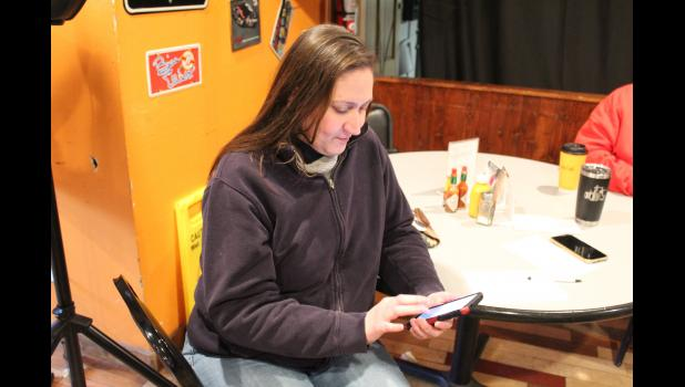 COMMERCIAL-NEWS   ROBERT TOMLINSON - Constantine resident Jennifer Bowerman fills out a submission form on her phone for Constantine to be featured on an upcoming HGTV show during an event held Saturday at the Harvey House Restaurant in Constantine.