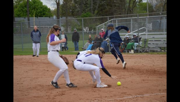 Commercial-News | Scott Hassinger - Gabby Charvat (11) of  Three Rivers fields a bunt while pitcher Ava Forman watches in Tuesday's second game of a doubleheader against Niles.