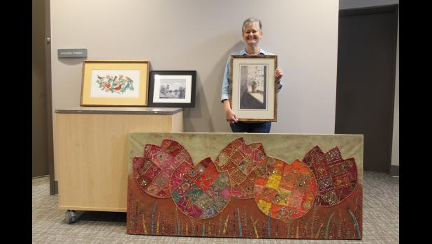 COMMERCIAL-NEWS   ROBERT TOMLINSON - St. Joseph County Commission on Aging Board of Directors member Sarah Apwisch shows off some of the art donated so far as part of the COA's Art Beautification Project, an effort started by Apwisch to display artwork and photography in the agency's Rivers Enrichment Center in Three Rivers.