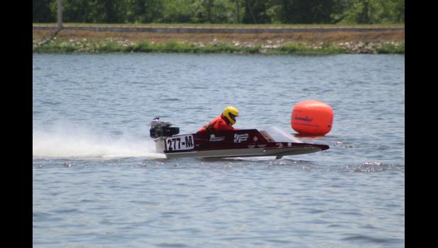 COMMERCIAL-NEWS | ROBERT TOMLINSON - Carl Armstrong of Three Rivers races on by the finish buoy during the annual Michigan Hydroplane Racing Association hydroplane boat racing competition in Constantine Sunday.