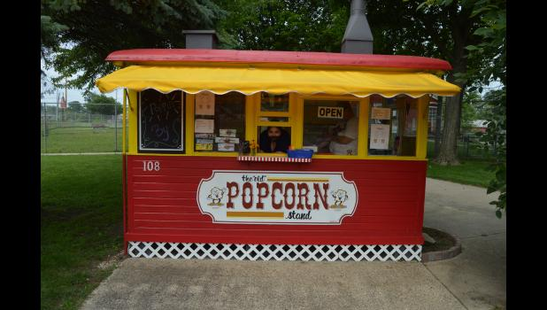 Commercial-News   Scott Hassinger - Tiffany Bennett, one of the six employees at the Popcorn Stand in Scidmore Park, peers out the window during her shift on Thursday as she waits for patrons.